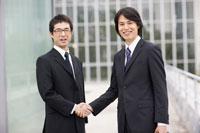 笑顔で握手するビジネスマン2人