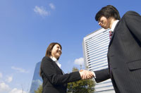 握手するビジネスマンとビジネスウーマン