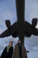 冬着のビジネスマンとビジネスウーマンと飛行機
