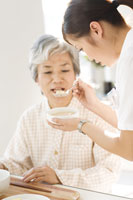 シニア女性患者の食事介助をする介護士