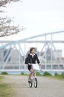 土手を自転車で走るビジネスウーマン