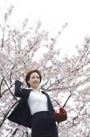 桜の下でキャッチボールするビジネスウーマン
