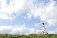 土手を自転車で走る女性