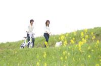 土手を散歩しているカップルと犬