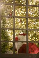 窓外に見えるプレゼントをかつぐサンタ