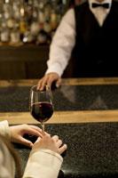 ワイングラスを持つ女性の手元とバーテンダー