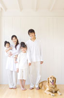 並んで立つ家族と犬
