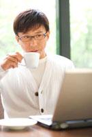 パソコンを見ながらコーヒーを飲む中高年男性