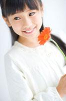 ガーベラを持っている笑顔の女の子 07135005045| 写真素材・ストックフォト・画像・イラスト素材|アマナイメージズ