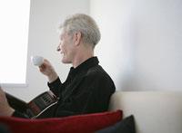 ソファでギターを抱えてコーヒーを飲む男性