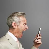 携帯電話を見て驚くビジネスマン