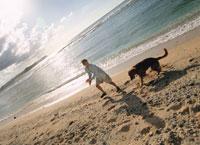 砂浜で遊ぶ女性と犬 20010000020A| 写真素材・ストックフォト・画像・イラスト素材|アマナイメージズ