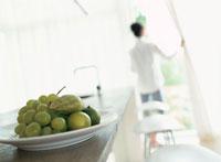 キッチンカウンターの上のフルーツと女性