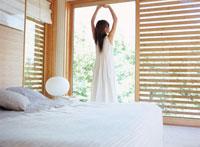 ベッドルームで背伸びをする女性