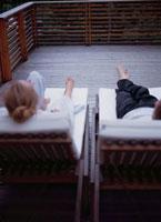 テラスのデッキチェアに横たわるカップル