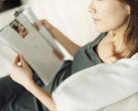 ソファで雑誌を見る女性