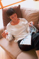 ソファで本を読む女性