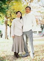 秋の公園に立つミドルカップル