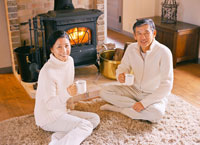 暖炉の前で飲み物を飲むミドルカップル