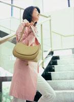 階段を昇るピンクのコートを着た女性