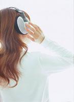 ヘッドフォンで音楽を聴く女性後姿