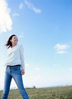 青空と草原に立つ女性