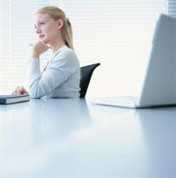 パソコンと頬杖をつく外国人女性