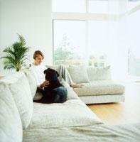 ソファでくつろぐ男性と犬