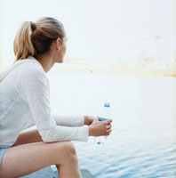 川岸でミネラルウォーターを持つ女性