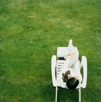 芝生の上の白いチェアーでリラックスする女性