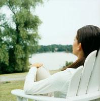 白い椅子に座る女性の後姿と湖