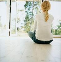 床に座り庭を眺める女性の後姿