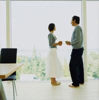 リビングの窓辺に立つ外国人カップル 20010001413| 写真素材・ストックフォト・画像・イラスト素材|アマナイメージズ