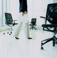 オフィス内を歩く女性とイス