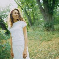 緑の森と白い服の女性