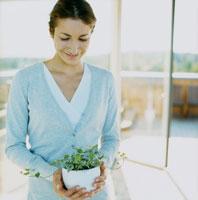 鉢植えのグリーンを持つ女性
