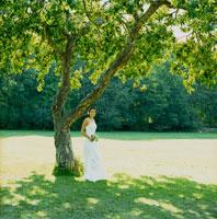 林檎の木の下でブーケを持つ花嫁