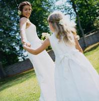 ウェデングドレスの花嫁と手をつなぐドレスの少女
