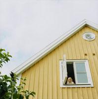 二階の窓から顔を出す女の子と空