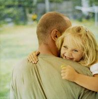 お父さんに抱きつく女の子の笑顔