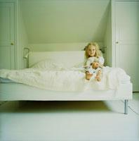白いベッドの上の女の子