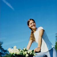 バラの花束をカゴに入れた自転車と女性