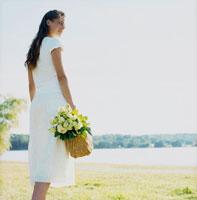 バラの花束を入れたバスケットを持つ女性
