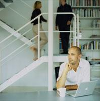 ノートパソコンの前の外国人男性と階段を上る男女
