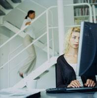 パソコンを見る外国人女性と階段を上る女性