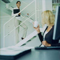 階段の女性と話すパソコンの前の女性後姿