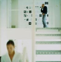 オフィスの中で携帯電話で話す男性と歩く女性