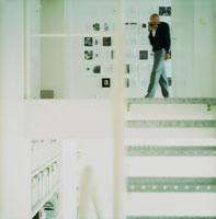 オフィスの中で歩きながら携帯電話で話す男性