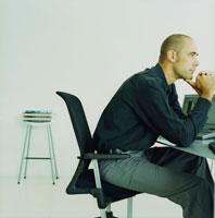 頬杖をついて座る外国人男性