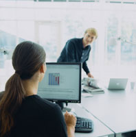 オフィスで話をする外国人男女とパソコン
